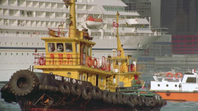 Tugboats and cruise ship in harbor / Hong Kong