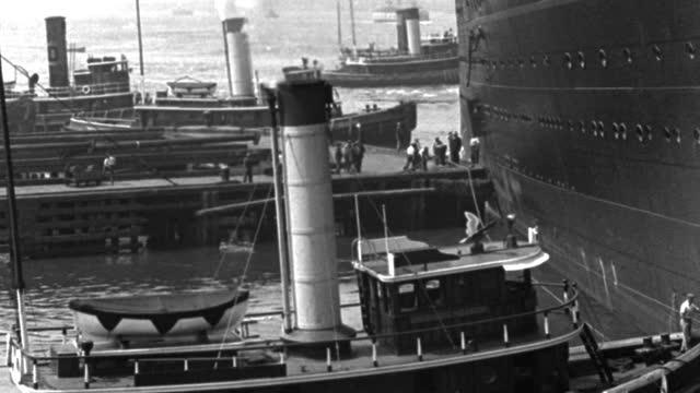 vídeos y material grabado en eventos de stock de tugboats dock near a 1930's ocean liner in new york harbor. - puerto de nueva york