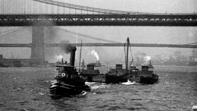 vidéos et rushes de tugboats docked in ny harbor / men and women passengers walking down gangplank to boat / boats in harbor brooklyn bridge clocktower building - pont de brooklyn