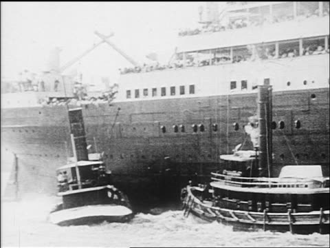 b/w 1912 tugboats pushing cruise ship out of harbor / newsreel - イングランド サウサンプトン点の映像素材/bロール