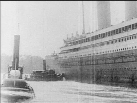 B/W 1912 tugboats pushing cruise ship out of harbor / newsreel