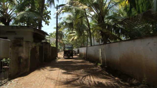 ms pov  tuk tuk cab driving through residential area / kochi, kerala, india - fahrradtaxi stock-videos und b-roll-filmmaterial