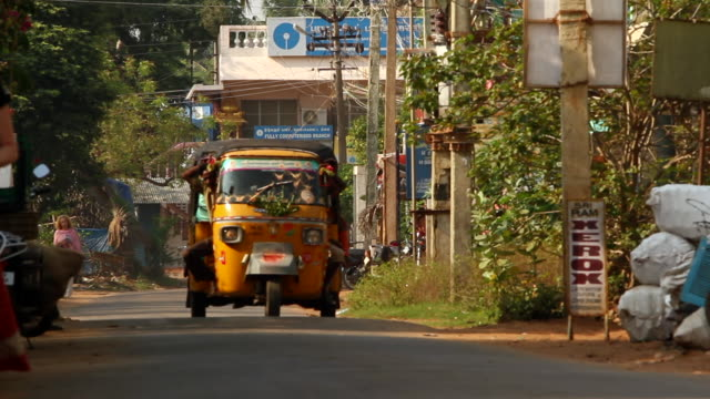 tuk tuk passes by on a street in pondicherry, india - jinrikisha stock-videos und b-roll-filmmaterial