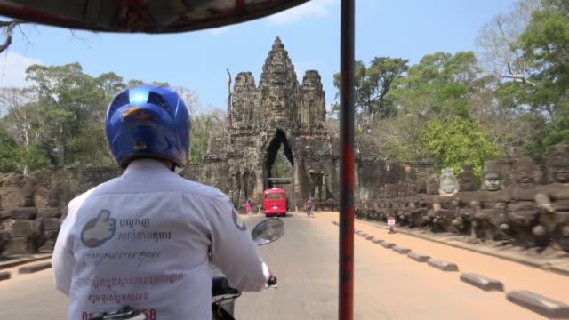 pov / a tuk tuk ride to south gate, entrance of angkor thom - jinrikisha stock-videos und b-roll-filmmaterial