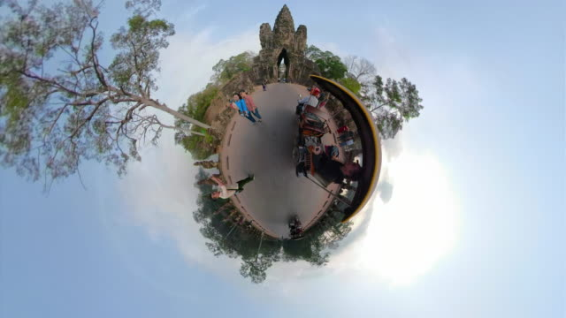 a tuk tuk ride to south gate, entrance of angkor thom with little planet effect - old ruin stock videos & royalty-free footage