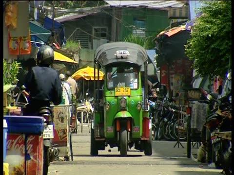 tuk tuk travels along busy road - auto rickshaw stock videos & royalty-free footage