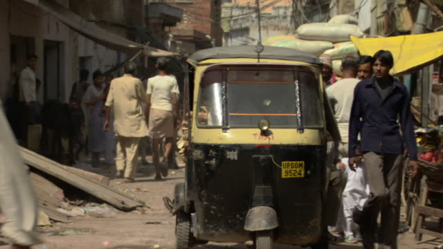 ms tuk tuk trying to make its way through crowds and merchant stalls on narrow street, agra, uttar pradesh, india - jinrikisha stock-videos und b-roll-filmmaterial