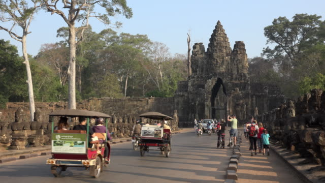 vídeos de stock e filmes b-roll de tuk tuks and tourists on causeway to south gate, entrance of angkor thom - camboja