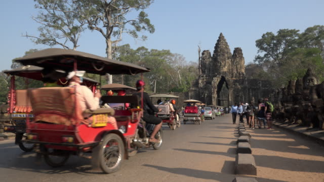 tuk tuks drive on causeway to south gate, entrance of angkor thom - angkor wat stock videos and b-roll footage