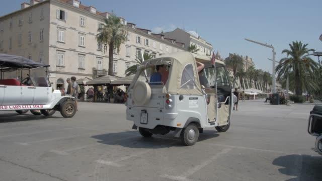 tuk-tuk, buildings and cafes on the promenade, split, dalmatian coast, croatia, europe - auto rickshaw stock videos & royalty-free footage
