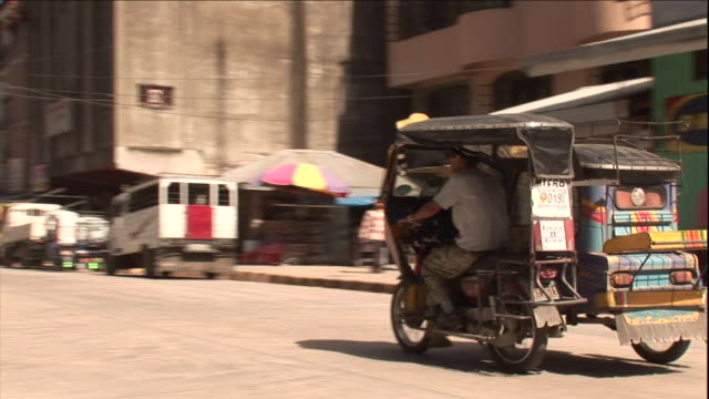 tuk-tuks pass each other on a busy street in bontuc, philippines. - risciò video stock e b–roll