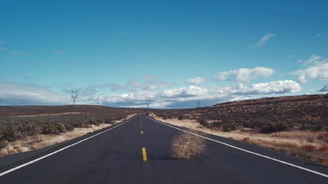 ws tumbleweed blowing across road / zillah, washington, usa  - 一つ点の映像素材/bロール