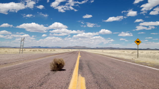 tumbleweed rolling on a rural highway - wild west stock videos & royalty-free footage