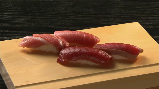 vidéos et rushes de tuna nigiri sushi lie on a wooden cutting board. - quatre objets