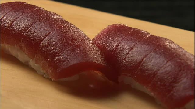 Tuna nigiri sushi lie on a wooden cutting board.