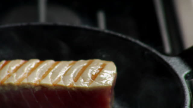 ecu, pan, tuna steak being cooked and turned in grill pan - fleischzange stock-videos und b-roll-filmmaterial