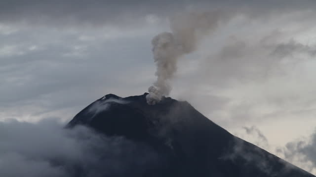 Tungurahua volcano spewing smoke, ash and fiery rocks.