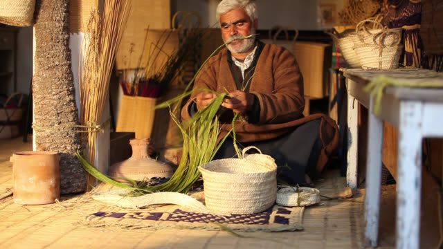Tunisian Basket Maker weaves basket in traditional way