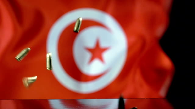 tunisian flag behind bullets falling in slow motion - dinar stock videos & royalty-free footage