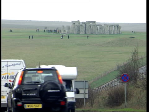 stockvideo's en b-roll-footage met tunnel plan to preserve stonehenge itv evening news chris ship somerset stonehenge traffic along busy road with stonehenge monument in b/g gv... - itv evening news