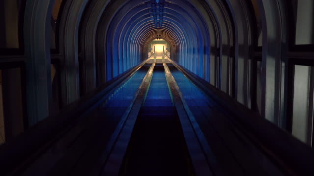 a tunnel with automated stairs and dark light in movement - escalator stock videos & royalty-free footage