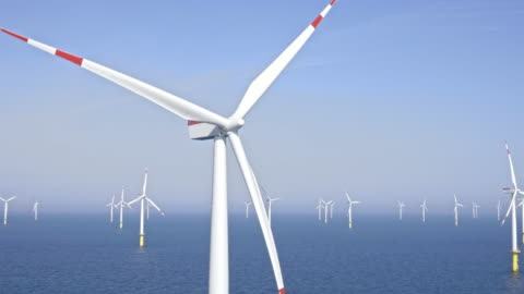 aerial turbine at offshore wind farm shining in the sun - wind turbine stock videos & royalty-free footage