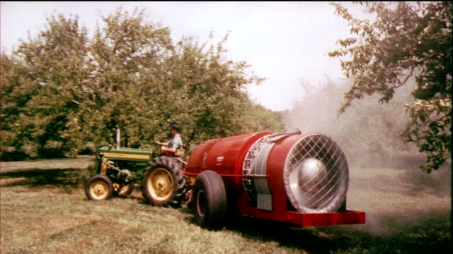 1958 cu zo pan ws turbine blades spinning, tractor pulling spraying equipment in orchard / usa / audio - insecticide stock videos & royalty-free footage