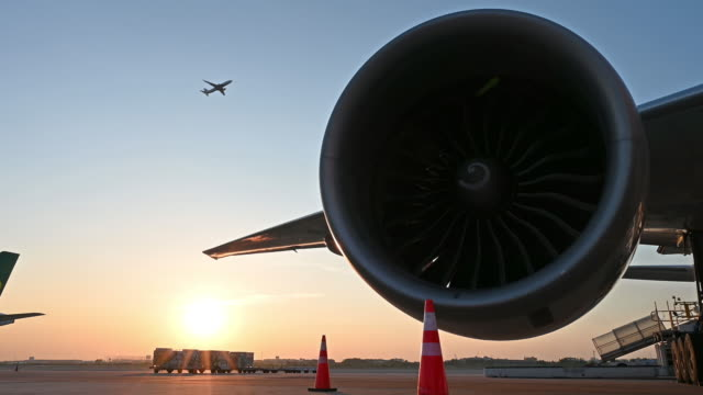 turbine engine of aircraft parked at the airport with sunset - cargo container stock videos & royalty-free footage