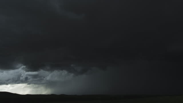 Turbulent supercell clouds pierced by a lightning flash roll above low hills, time lapse
