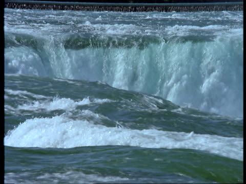 turbulent water flows over the edge of niagara falls. - fluss niagara river stock-videos und b-roll-filmmaterial