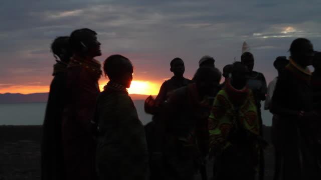 turkana people singing and dancing at sunset, north kenya