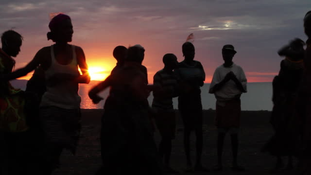 turkana people singing and dancing at sunset, north kenya
