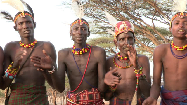 Turkana warriors chant as a woman performs a traditional tribal dance.
