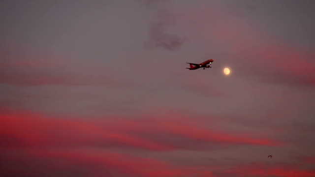 Turkish Airlines approaching to Ataturk International Airport in Istanbul during the sunset with the moon visible on the sky