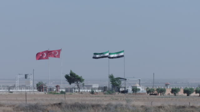 turkish and syrian flags near refugee camp - syrien stock-videos und b-roll-filmmaterial