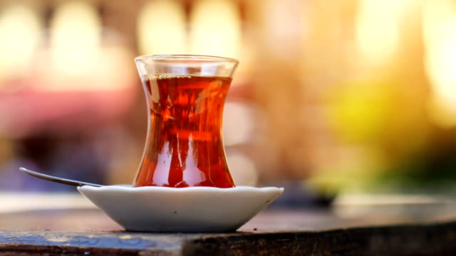 Turkish black tea on a sidewalk tea house table with unrecognizable blurry people on the background