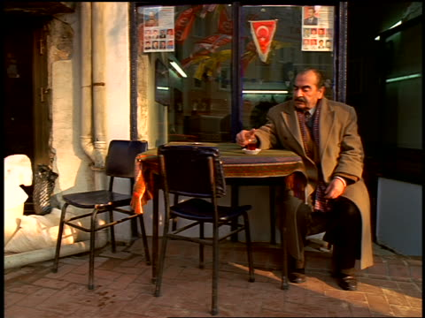vidéos et rushes de turkish businessman in overcoat sitting at table drinking in front of store/cafe / istanbul, turkey - moustache