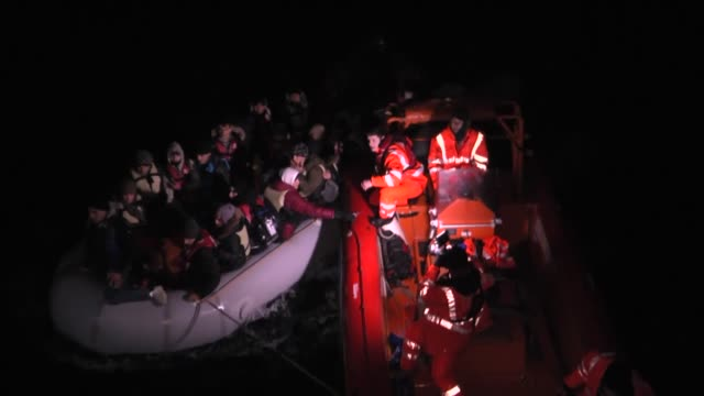 vídeos de stock e filmes b-roll de turkish coast guard members intervene in a boat carrying refugees who were trying to go to greek islands after being caught by the tcsg 'guven' ship... - crise de migrantes europeia 2015 2016