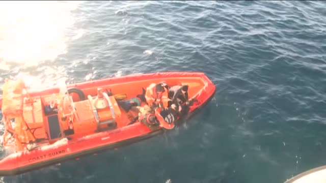 turkish coast guard personnel help refugees as they swim with buoys after they toppled over a fishermen dinghy en route to greece on january 22 2016... - aydın province stock videos and b-roll footage