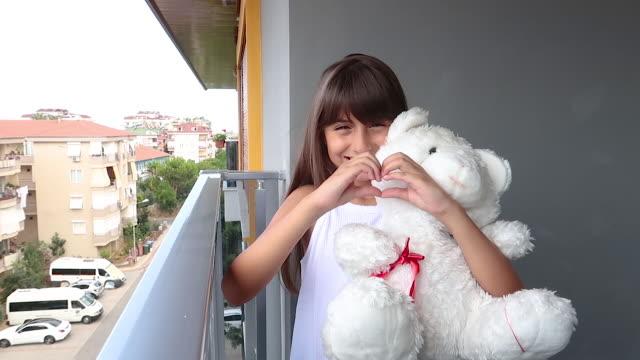 バルコニーで彼女のテディとポーズトルコのかわいい女の子 - 遊具点の映像素材/bロール