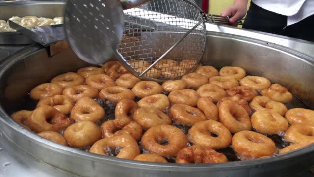 vídeos y material grabado en eventos de stock de donuts de postre turco, masa dulces, hacer y freír lokma postre en una gran sartén en aceite funeral regalando alimentos lokma, baklava turco - waffles