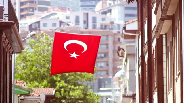 vidéos et rushes de drapeau turc est en agitant sur une corde suspendue entre les bâtiments à structure résidentielle sur le fond - drapeau turc