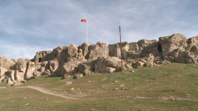 turkish flag swinging on top of rock formation in cappadocia, turkey - rock hoodoo stock videos & royalty-free footage