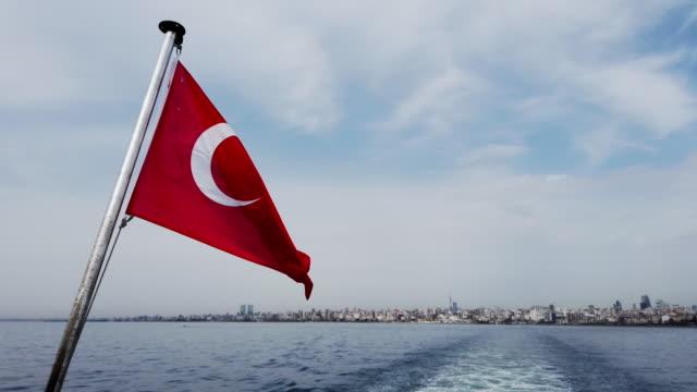 vidéos et rushes de drapeau turc agitant derrière le navire et vue de ville d'istanbul à l'arrière-plan - drapeau turc