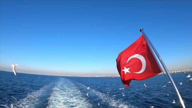 vidéos et rushes de drapeau turc ondulant dans le paysage de mer au ralenti - drapeau turc