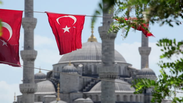 vidéos et rushes de ms turkish flags flapping on wind, sultan ahmed mosque (blue mosque) in background / istanbul, turkey - drapeau turc