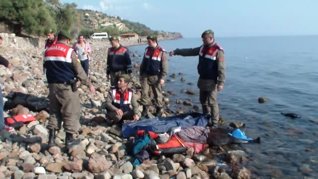 vídeos de stock e filmes b-roll de turkish gendarmerie carry the bodies of refugees after a boat carrying refugees sank off close to coast of ayvacik district canakkale turkey on... - crise de migrantes europeia 2015 2016