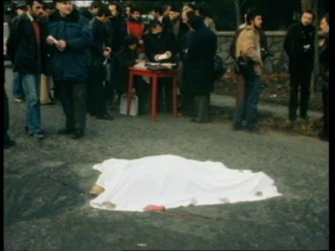 Istanbul MS Blanket draped body of Prof Cavit Orhan Tutengil on ground CMS Wrist of dead man protruding from blanket