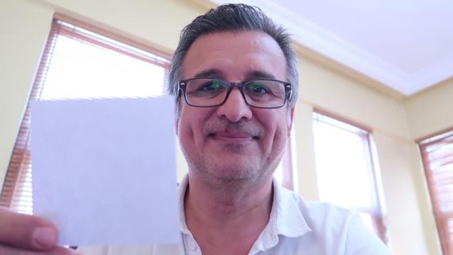 stockvideo's en b-roll-footage met turkse knappe mens die lege nota toont - onbeschreven