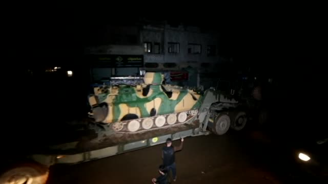 vídeos de stock e filmes b-roll de a turkish military convoy passes overnight through the town of binnish in rebel held idlib province and heads in the direction of idlib city to the... - southwest usa